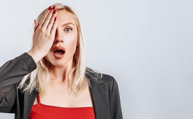 Zaskoczona blondynka zakrywa dłonią połowę twarzy