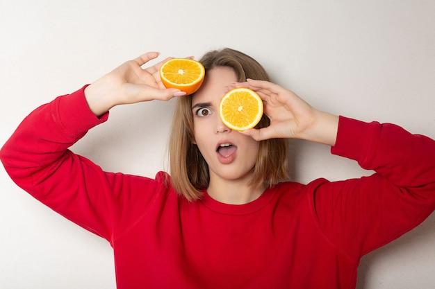 Zaskoczona brunetka pozuje z połową pomarańczy, zasłaniając oczy pomarańczą na białej ścianie