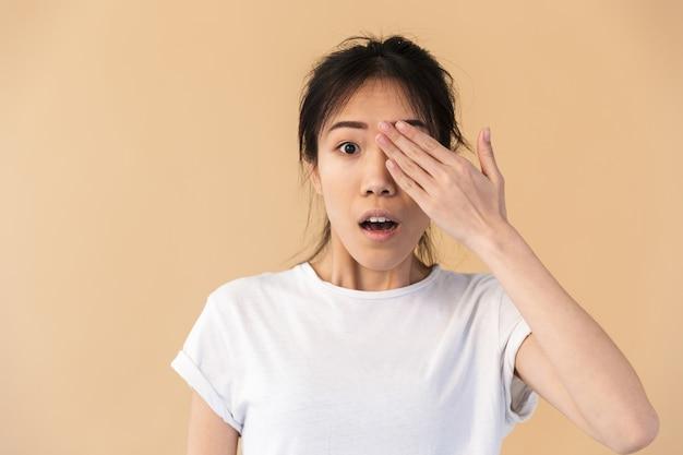 Zaskoczona chińska kobieta ubrana w prosty t-shirt zakrywający oczy i zerkający na beżową ścianę w studio