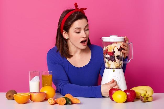 Zaskoczona ciemnowłosa kobieta z czerwoną opaską, włącza przycisk robota kuchennego wypełnionego kawałkami różnych owoców, robi smaczny deser, siada przy kuchennym stole agaisnt różowy. diety