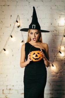 Zaskoczona czarownica z koszem z dyni