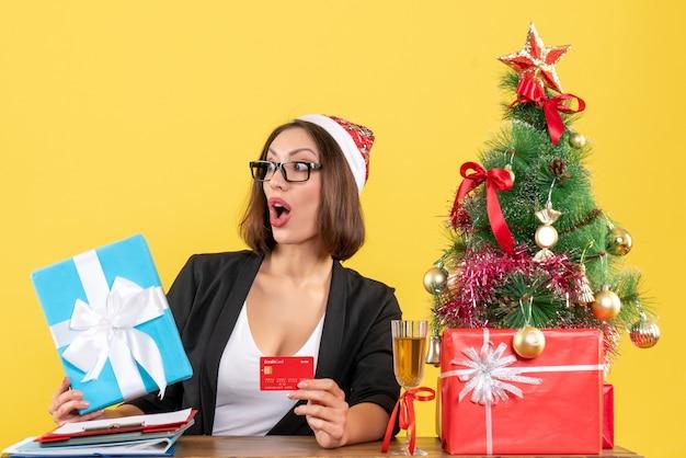 Zaskoczona czarująca dama w garniturze z czapką świętego mikołaja i okularami pokazująca prezent i kartę bankową w biurze na żółtym tle