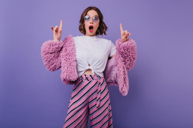Zaskoczona czarująca kobieta w pasiastych spodniach, pozowanie na jasnej fioletowej ścianie. wewnątrz portret emocjonalnej dziewczyny z falującymi włosami, wyrażającej zdumienie.