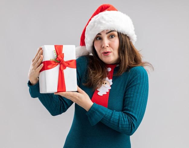 Zaskoczona dorosła kaukaska kobieta w kapeluszu świętego mikołaja i krawacie świętego mikołaja trzymająca pudełko na prezent świąteczny na białym tle na białej ścianie z miejscem na kopię