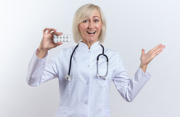 Zaskoczona dorosła słowiańska lekarka w szacie medycznej ze stetoskopem trzymająca tabletkę z lekiem w blistrze i trzymająca otwartą dłoń na białym tle z kopią miejsca