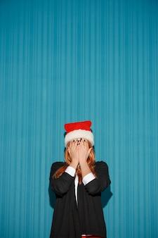 Zaskoczona dziewczyna boże narodzenie w kapeluszu santa na niebieskim tle