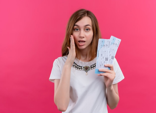 Zaskoczona dziewczyna młody podróżnik trzymając bilety lotnicze na na białym tle różowej ścianie z miejsca na kopię