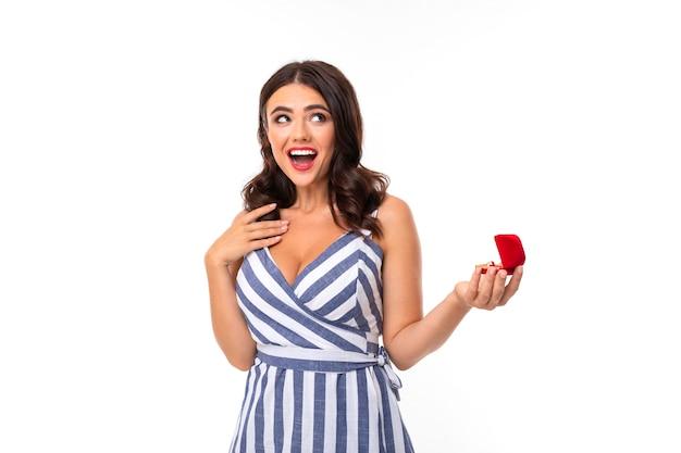 Zaskoczona dziewczyna o brązowych włosach w sukience z dekoltem trzyma pudełko z pierścionkiem zaręczynowym