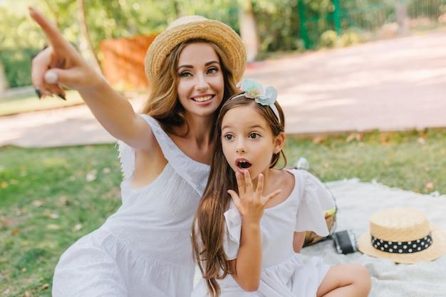 Zaskoczona dziewczyna o dużych ciemnych oczach patrzy tam, gdzie jej matka wskazuje palcem. urocza młoda kobieta z długimi kręconymi włosami, bawiąc się z śliczną brunetką, nosi wstążkę.