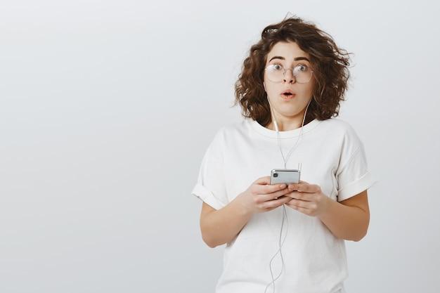 Zaskoczona dziewczyna patrzy zdumiona, jak trzyma telefon komórkowy i nosi słuchawki