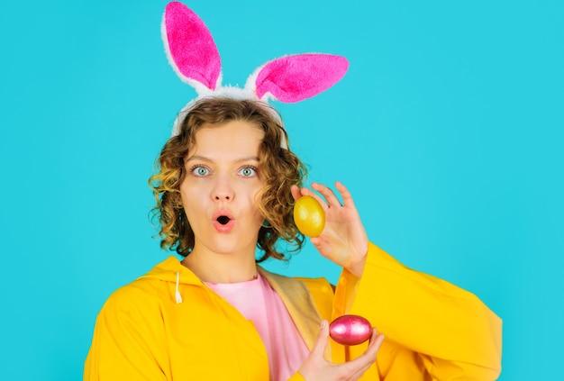 Zaskoczona dziewczyna ubrana na żółto i z uszami królika trzymająca kolorowe jajka na jasnoniebieskim tle