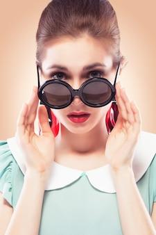 Zaskoczona dziewczyna w okrągłych okularach przeciwsłonecznych
