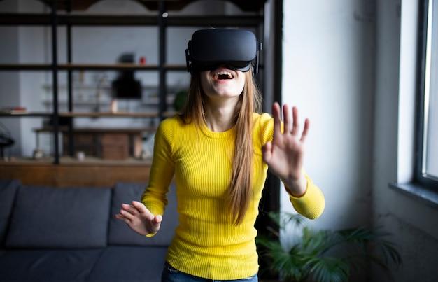 Zaskoczona dziewczyna w okularach vr. dotyka czegoś i wyraża emocje wynikające z tego doświadczenia. łał