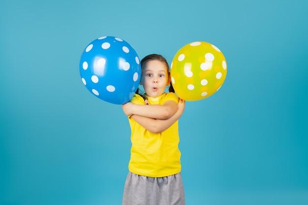 Zaskoczona dziewczyna w żółtym t-shircie z otwartymi ustami warkoczykami przytula się i trzyma balony