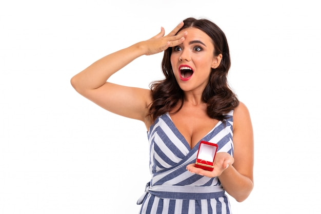 Zaskoczona dziewczyna z brązowymi włosami w sukience z dekoltem trzyma pudełko z pierścionkiem zaręczynowym na białym tle z copyspace