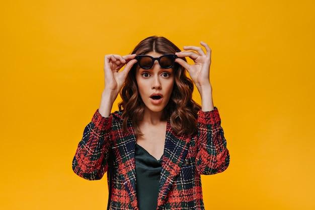 Zaskoczona dziewczyna z falującymi włosami w pasiastej kurtce zdejmuje okulary na izolowanej ścianie