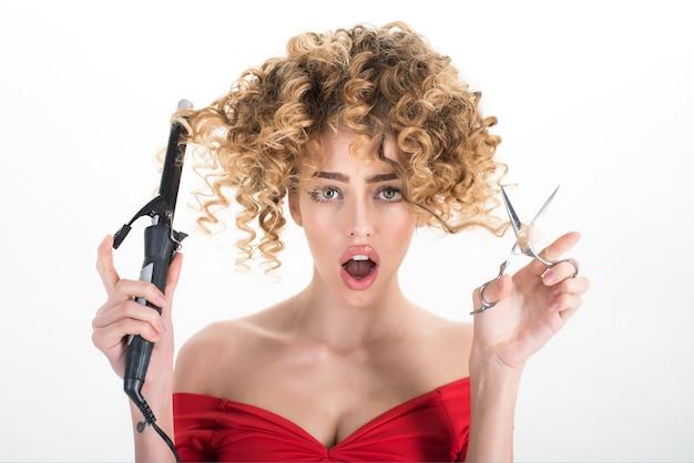 Zaskoczona dziewczyna z kręconymi włosami trzyma sprzęt fryzjerski fryzjer przemysł kosmetyczny zawód makijaż