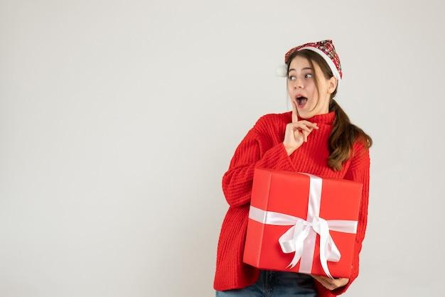 Zaskoczona dziewczyna z santa hat trzymając ciężki prezent stojący na białym tle