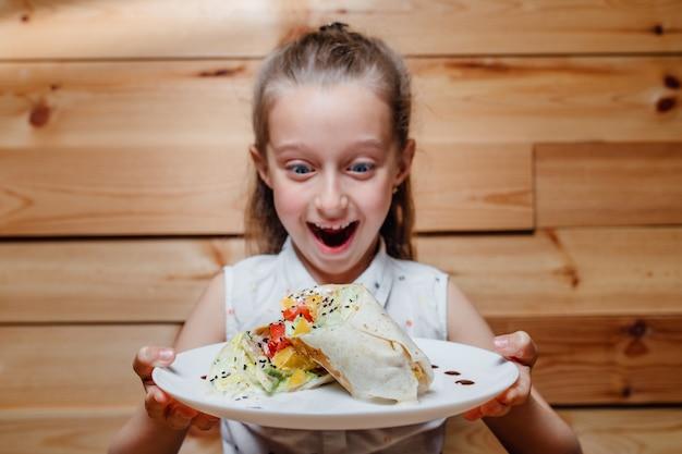 Zaskoczona dziewczynka z wegetariańską górą lodową wrap