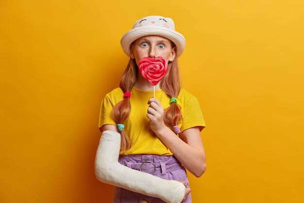 Zaskoczona dziewczynka zakrywa usta dużym lizakiem, cieszy się latem, lubi słodycze i trzyma pyszne cukierki, ubrana w stylowy strój, ma złamaną rękę, odizolowaną na żółtej ścianie.