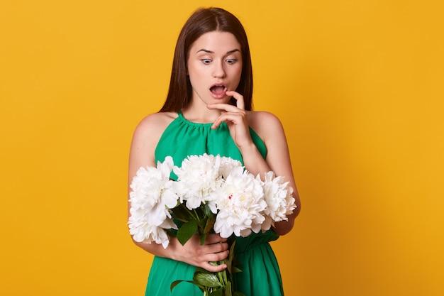 Zaskoczona emocjonalna dama, patrząc na bukiet białych piwonii, szeroko otwierając usta i oczy, dotykając palcem policzka, będąc pod wrażeniem wiosny, zgadując, czyj to prezent.