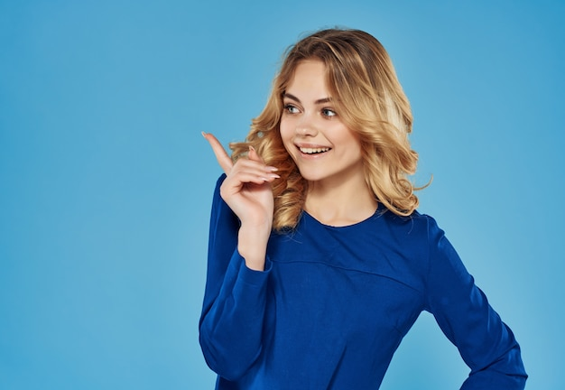 Zaskoczona emocjonalna kobieta w niebieskiej sukience gestykuluje z niebieskim tłem dłoni