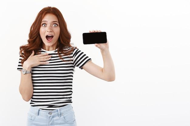 Zaskoczona, entuzjastyczna młoda rudowłosa grająca w gry wygląda na zaniemówioną i robi wrażenie, nie może zdać sobie sprawy, że ubiła rekord, pokazując poziomo wyświetlacz smartfona, dysząc z podziwu i zdumienia