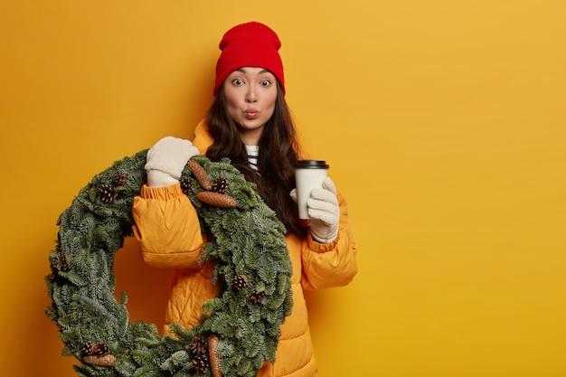 Zaskoczona etniczna kobieta pije aromatyczną kawę, nosi ręcznie robiony świąteczny wieniec, ubrana w zimową odzież, białe rękawiczki utrzymują zaokrąglone usta