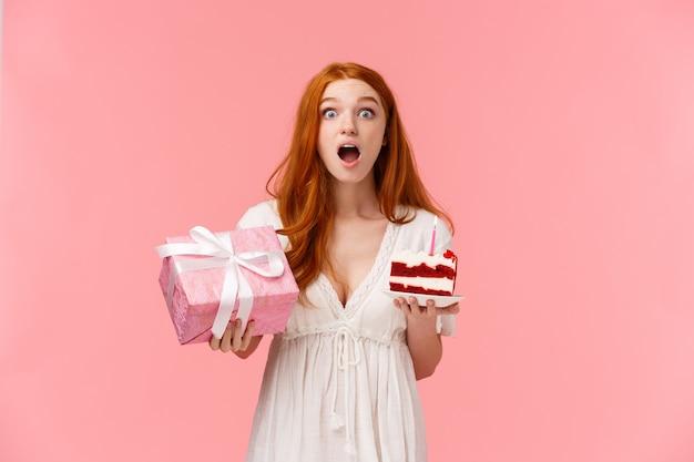 Zaskoczona i ciekawa zdziwiona śliczna ruda kobieta reagująca na niesamowity prezent