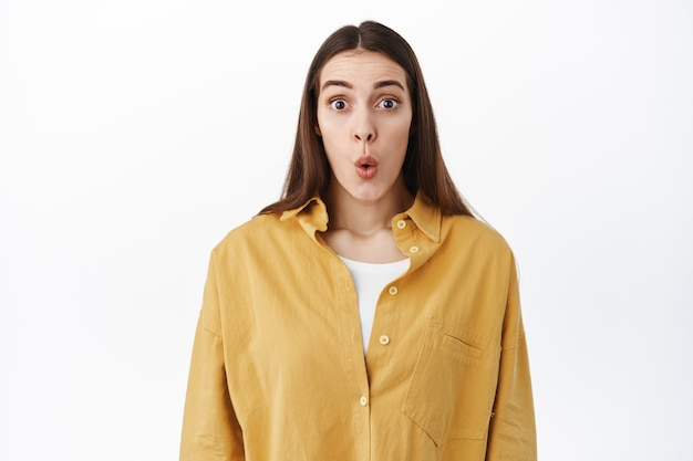 Zaskoczona i podekscytowana kobieta unosi brwi i składa usta pod wrażeniem, sprawdza coś niesamowitego, gapi się na niesamowitą ofertę promocyjną, wygląda na zafascynowaną, stoi nad białą ścianą