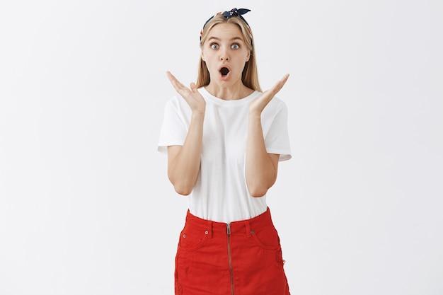 Zaskoczona i podekscytowana młoda blond dziewczyna pozuje pod białą ścianą