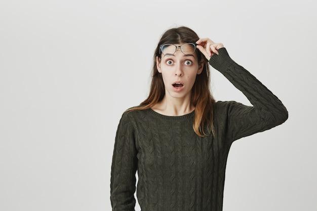 Zaskoczona i podekscytowana, zszokowana kobieta zdejmuje okulary i patrzy z opuszczoną szczęką