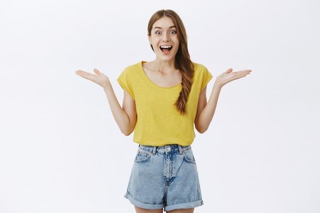 Zaskoczona i rozbawiona charyzmatyczna atrakcyjna kobieta w żółtej koszulce, wzruszająca ramionami z rękami rozłożonymi w pobliżu ramion, otwarte usta uśmiechnięte radośnie