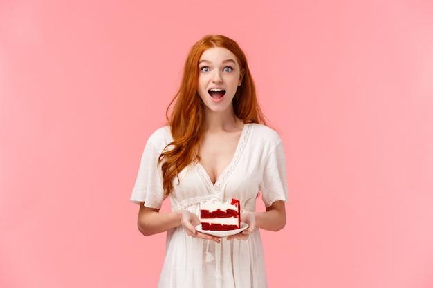 Zaskoczona i rozbawiona charyzmatyczna ruda kobieta plotkuje podczas imprezy, trzymając talerz z ciastem