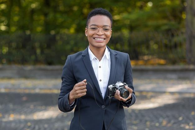 Zaskoczona i szczęśliwa afroamerykanka patrzy w kamerę i uśmiecha się trzymając kamerę filmową podczas spaceru po parku