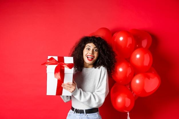 Zaskoczona i szczęśliwa kobieta trzymająca prezent walentynkowy od kochanka, stojąca w pobliżu balonów romantycznych serc i patrząc na aparat zdziwiony, czerwone tło.