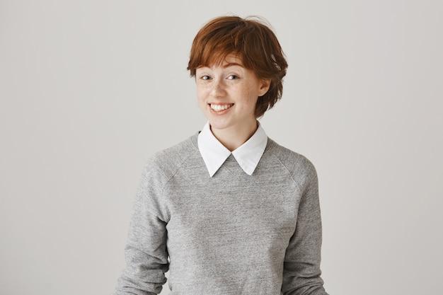 Zaskoczona i szczęśliwa ruda dziewczyna z krótką fryzurą, pozowanie na białej ścianie