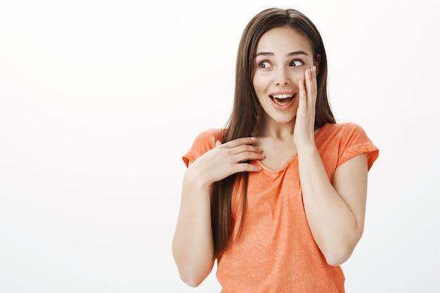 Zaskoczona i wdzięczna śliczna brunetka dziewczyna trzymająca się za serce, wyglądająca na zadowoloną lub wdzięczną