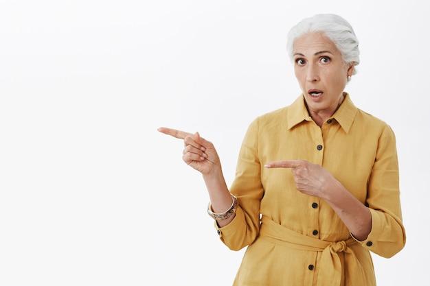 Zaskoczona i zaskoczona babcia wskazująca w lewo, dysząc zdumiona