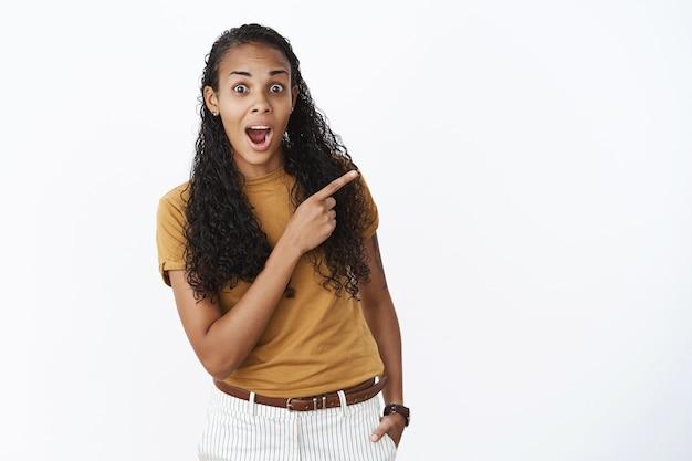 Zaskoczona i zdumiona afroamerykanka w brązowej koszulce