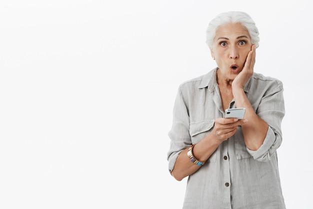 Zaskoczona i zdumiona starsza pani szuka i trzyma smartfona
