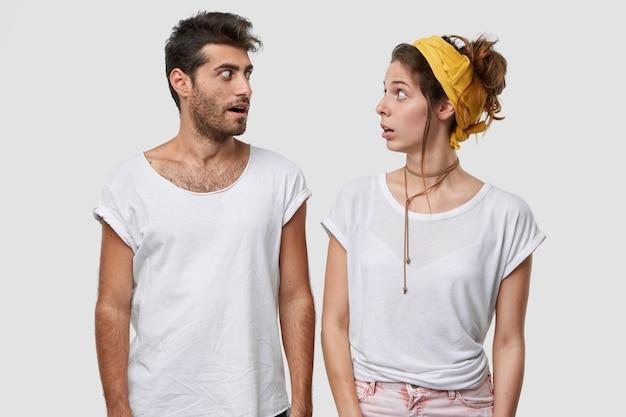 Zaskoczona kobieta i mężczyzna rozmawiają o czymś niewiarygodnym, patrzą szeroko otwartymi oczami, mają zaskakujący wyraz twarzy, noszą zwykłą białą koszulkę, modelują w pomieszczeniach
