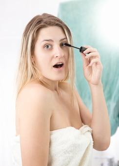 Zaskoczona kobieta nakłada makijaż w łazience