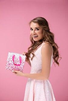 Zaskoczona kobieta otwiera torbę na prezent gift