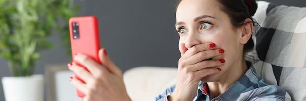 Zaskoczona kobieta patrząca na ekran smartfona zakrywająca usta ręką nowego smartfona