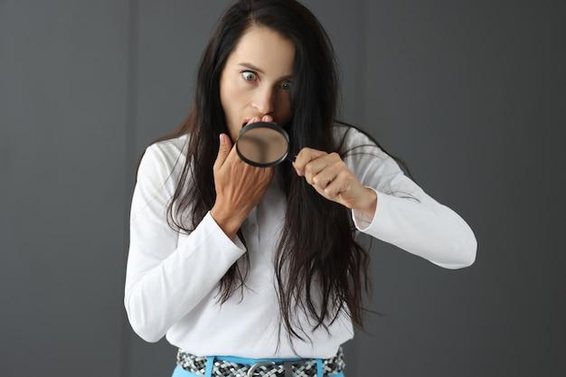 Zaskoczona kobieta patrząca przez szkło powiększające i zakrywająca usta nie znaleziono strony dłoni