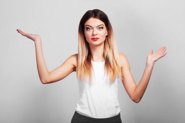 Zaskoczona kobieta pokazuje swój produkt ręką na szarej ścianie