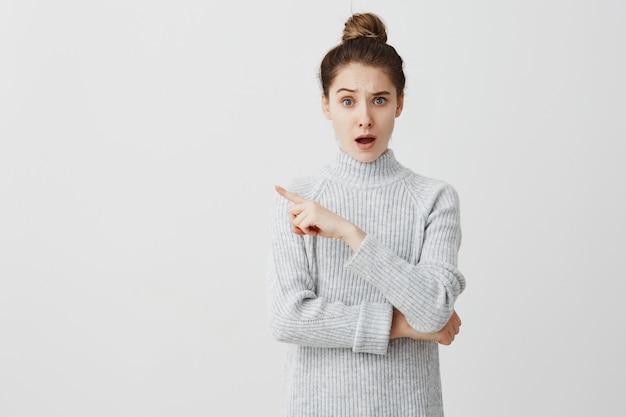 Zaskoczona kobieta przerażona czymś okropnym i pokazująca się na tym. młoda mama wyraża oburzenie, gestykulując, co jej dziecko zrobiło stojąc nad białą ścianą. koncepcja frustracji