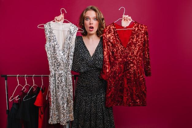 Zaskoczona kobieta trzymająca błyszczące sukienki, dokonująca wyboru stroju na imprezę