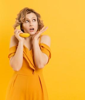 Zaskoczona kobieta używa banana jako telefonu komórkowego